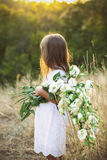 Little girl in a meadow with white wild summer flowers Stock Photos