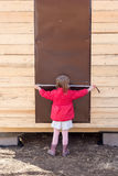 Little girl measures the door with tape measure Royalty Free Stock Image