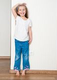 Little girl measures the growth. Near the wall at home Stock Images
