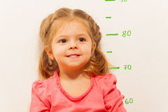 Little girl measuring height against wall in room Royalty Free Stock Image