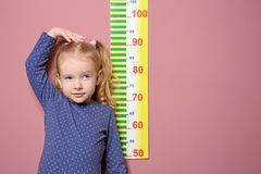 Little girl measuring her height on background. Little girl measuring her height on color background royalty free stock photo