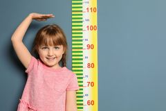 Little girl measuring her height. On color background stock photo
