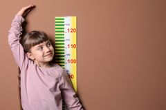 Little girl measuring her height. On color background royalty free stock photos