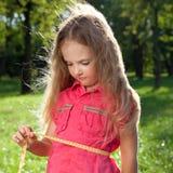Little girl measuring her waist Royalty Free Stock Photo
