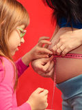 Little girl measuring mother's tummy Royalty Free Stock Photos