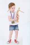Little girl with medal on chest stands and holds wooden dummy Royalty Free Stock Images