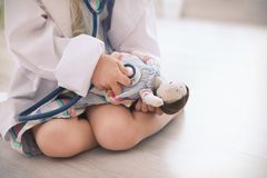 Little girl in medical coat playing with doll. On floor royalty free stock photography