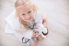 Little girl in medical coat playing with doll. On floor stock images