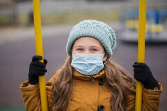 Little girl in medical mask on swing. At atumn playground