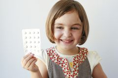 Little girl with medicaments in her hand Stock Photo