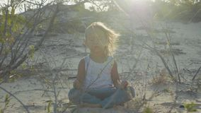 Little girl meditates at desert. Child sitting on the sand at sunset warm. Little cute girl meditates at desert. Child sitting on the sand at sunset warm light stock video