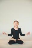 Little girl meditating. Little girl doing yoga on white background Stock Image