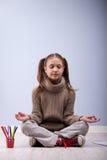 Little girl meditating instead of making homework Stock Images