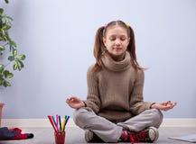 Little girl meditating instead of making homework Stock Photo