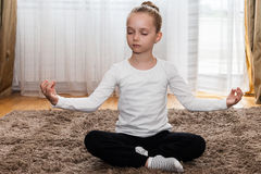 Little girl in meditating position Royalty Free Stock Image