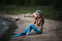 Little girl Mermaid with seashell. Is dreaming on the sunset royalty free stock photo