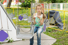Little girl on a merry-go-round eating candy Stock Image