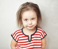 Little girl with messy hair and calm face expression. Little girl with beautiful big brown eyes, messy hair and calm friendly face expression in striped T-shirt Royalty Free Stock Photography
