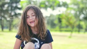 Little girl with messy hair, in the park , laughing; positive emotions. Beautiful little girl with messy hair, in the park , laughing; positive emotions stock footage