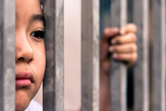Little girl with metal fence, feeling no freedom. Stock Photo