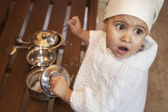 Little girl with metal ladle and cook hat Stock Photography