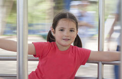 Little girl on metal playground carousel stock photo
