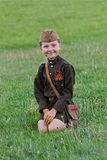 A little girl in a military uniform sitting on the grass on Victory Day celebration in Volgograd Stock Photography