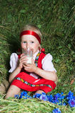 The little girl with a milk glass on hay Stock Photo