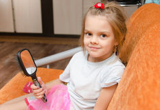 Little girl with a mirror sits on the couch Royalty Free Stock Photography