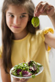 Little girl with mixed salad. Looking worried at it Stock Photos