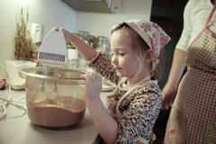 Little girl mixing dough for a birthday cake Stock Images