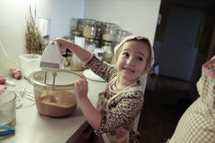 Little girl mixing dough for a birthday cake Stock Photography