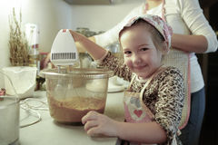Little girl mixing dough for a birthday cake Royalty Free Stock Images