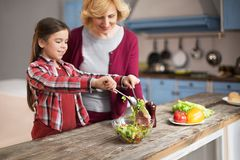 Grandmother and cute granddaughter cooking salad. Little girl mixing salad with two spoons on big wooden table. Grandmother looking at her Stock Photo
