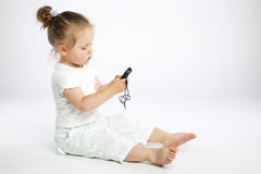 Little girl with mobile phone. On gray background Royalty Free Stock Photography