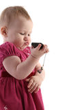 Little girl with mobile phone. Little girl in red jacket with mobile phone in hand, isolated on white background Royalty Free Stock Image