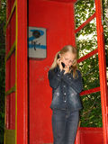 Little girl with mobile phone. Little girl in the old public call-box with mobile phone Royalty Free Stock Photography