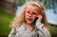 Little girl with mobile phone. Portrait of a cute blonde girl with mobile phone Stock Photography