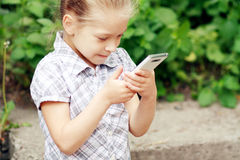 Little girl with mobile phone Stock Photos