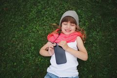 Little girl with mobile phone on the grass Royalty Free Stock Photos