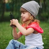 Little girl with mobile phone on the grass Royalty Free Stock Photo