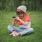 Little girl with mobile phone on the grass Stock Images