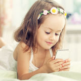 Little girl with mobile phone in her hands Royalty Free Stock Photography