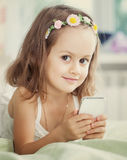 Little girl with mobile phone in her hands Royalty Free Stock Photos