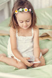 Little girl with mobile phone in her hands Stock Photo
