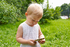 Little girl with a mobile phone outdoor Royalty Free Stock Images