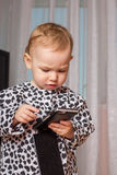 Little girl with a mobile phone. The little girl presses a button on your smartphone Stock Photo