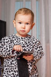 Little girl with a mobile phone. The little girl presses a button on your smartphone Royalty Free Stock Images