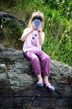 Little girl with mobile phone on rocks Royalty Free Stock Image