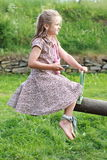 Little girl with a mobile phone on a swing. Barefoot little girl in a flowered dress holding a mobile phone on a swing Royalty Free Stock Photos